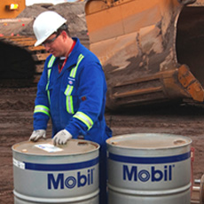 Worker With Barrels Of Mobil Oil